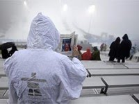 Spectator reads newspaper in the rain